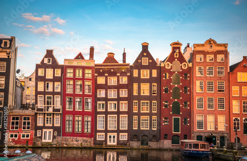 Traditional old buildings and boats at sunset in Amsterdam, Netherlands Wallpaper Mural