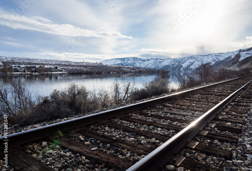 Photo Railroad tracks running along the snow covered Columbia river valley north of We