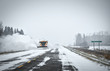 A snowplow vehicle driving along a highway clearing billowing clouds of snow off in a winter snow storm