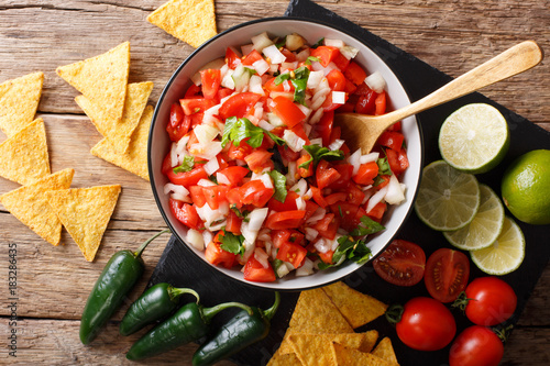 Homemade spicy pico de gallo close-up in a bowl and nachos. horizontal top view