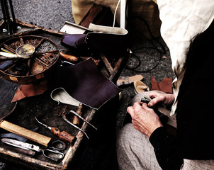 workshop with expert shoemaker during the repair of shoes with p
