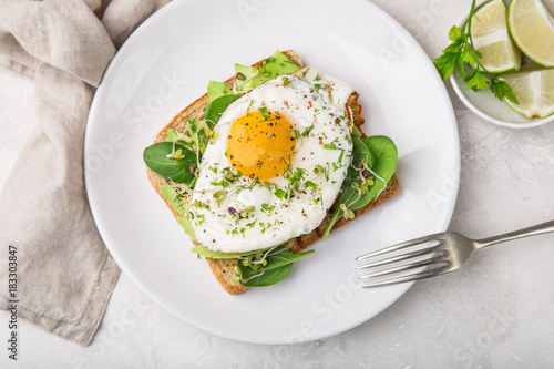 Fotografía  toast with avocado, spinach and fried egg