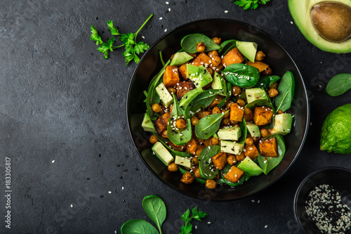 Photo  Avocado, quinoa, roasted sweet potato, spinach and chickpeas salad in black bowl