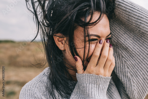 Fotografia  Closeup cropped portrait of happy and funny brunette woman smiling and laughing with hand on mouth, against nature meadow background with windy hair