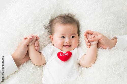 両親と手をつなぐ赤ちゃん Canvas Print