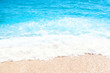 Soft wave of blue ocean on sandy beach Background with place for text. Tropical summer vacation concept..Soft wave of blue ocean