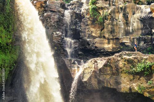 Photo  woman particing asana yoga in waterfall in bali. indonesia