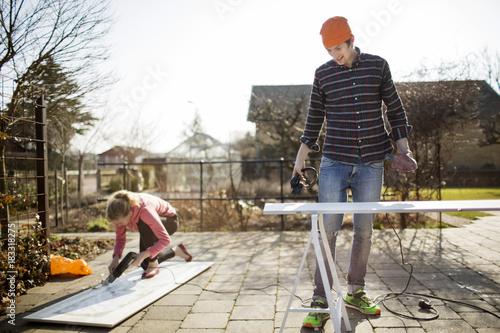 Papiers peints Statue Couple doing DIY in garden