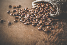 Brown Beans With Burlap Bag On The Wooden Table. Harvest Of Coffee In Different Countries. Choice Of The Best Sort And Quality Coffee. Rustic Atmosphere. Advertising Concept.