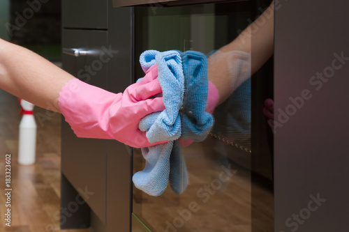 Employee hand in rubber protective glove with micro fiber cloth wiping an electric oven surface Fototapeta