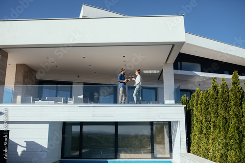 Couple enjoying sunny day on modern house terrace