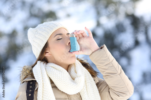 Photo Woman using asthma inhaler in a cold winter