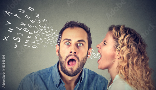 Canvastavla Angry woman screaming something in the ear of a shocked, scared guy isolated on gray wall background