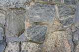 The texture of the old, wet granite in the masonry of the wall