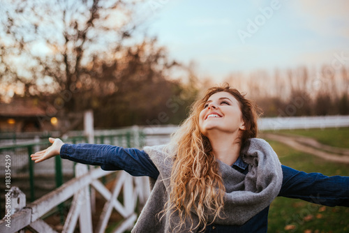 Fotografia  Freedom feel good. Joyful woman rising hands outside.