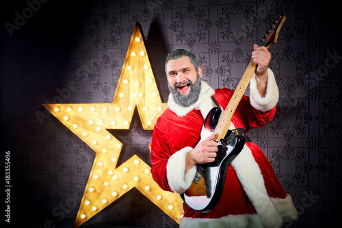 Fotografie, Obraz  Happy Santa with a guitar is dancing against the background of a big electric star in Christmas