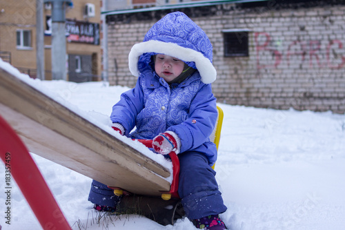 Fototapeta little girl swinging on a swing in a playground on a winter day obraz na płótnie