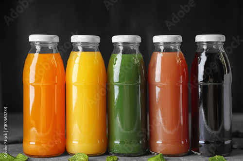 Photo  Bottles of fresh juices on table against black background