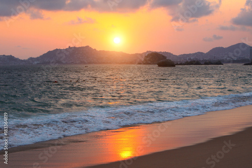 Fototapeta Sunset, ocean waves and beach, Acapulco, Mexico
