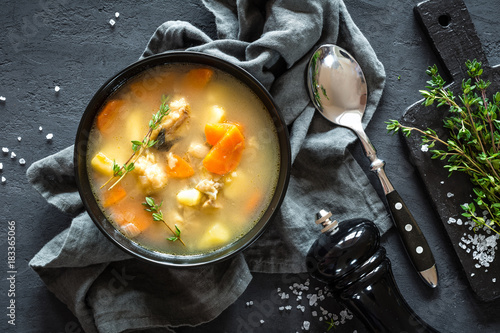 Fotografie, Tablou Fresh fish soup in bowl on dark background, top view