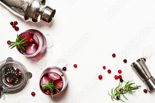 Photo sur Aluminium Cocktail Red cranberry cocktail with ice, rosemary and vodka, bar tools, white background, top view