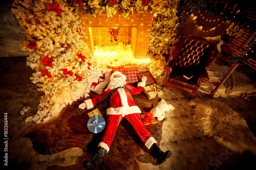 Fotografering  Santa Claus is lying drunk tired on the floor by the fireplace after Christmas