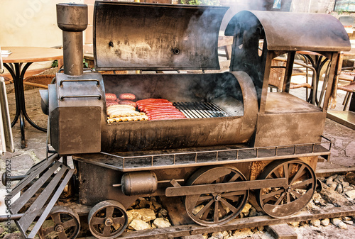 Photo  Barbecue grill with meat in shape of steam locomotive, yellow filter