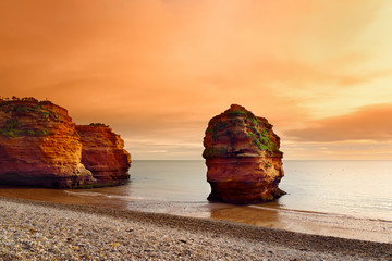Fototapeta Słynne budowle i znane miejsca Impressive red sandstones of the Ladram bay on the Jurassic coast, a World Heritage Site on the English Channel coast of southern England, Devon