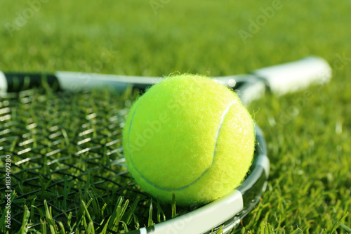 Tennis racket and ball on green grass