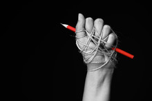 Hand With Red Pencil Tied With...