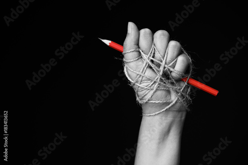 Fotografia  Hand with red pencil tied with rope, depicting the idea of freedom of the press or freedom of expression on dark background in low key