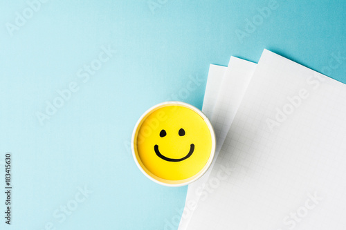 Yellow smiling face, happy mood, on paper cup and papers over blue background Wallpaper Mural