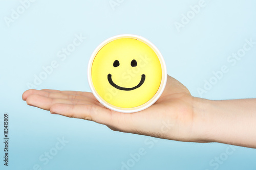 Canvas Print Hand giving hapiness concept. Yellow happy face emoticon.