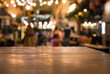 Wood table top with blur of lighting in night cafe restaurant background/selective focus.