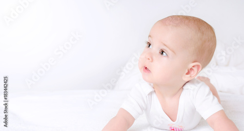 Fototapety, obrazy: Cute baby with beautiful brown eyes lying in white bed