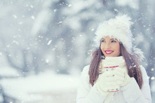 Beautiful Smiling Young Woman In Warm Clothing With Cup Of  Hot Tea Coffee Or Punch. The Concept Of Portrait In Winter Snowy Weather