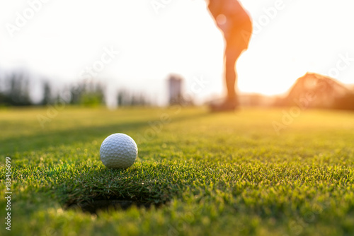 Poster Golf Golfer asian woman putting golf ball on the green golf on sun set evening time, select focus. Healthy and Lifestyle Concept.