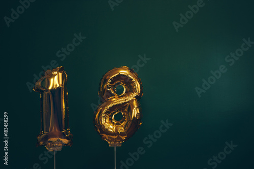 Photo Hands holding golden 18 balloons, new year concept