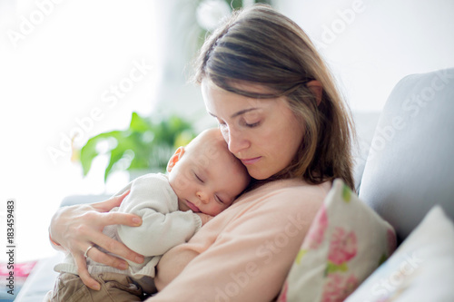 Young mother, holding tenderly her newborn baby boy