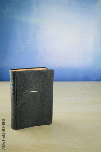 Valokuva  Ein kirchliches Gesangbuch auf einem Holztisch, dahinter blauer Himmel, Textfrei