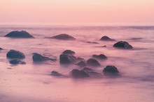 Summer Seasonal Natural Vacation Background. Romantic Morning At Sea. Big Boulders Sticking Out From Smooth Wavy Sea. Long Exposure.