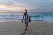 Woman Wearing A Christmas Santa Hat Walking On Beach Carrying A Pineapple, Haleiwa, Hawaii, America, USA