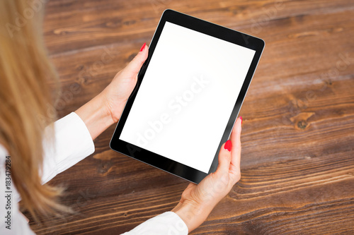 Fotografia  Woman holding tablet on wooden table.