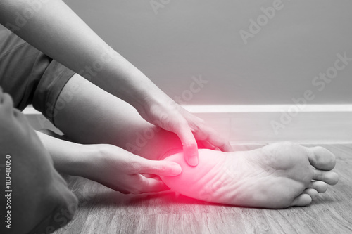 Fotografia  Female foot heel pain with red spot, plantar fasciitis