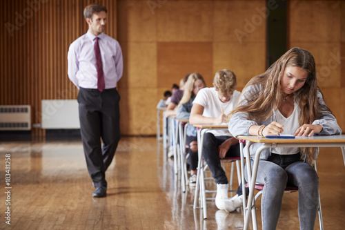Valokuvatapetti Teenage Students Sitting Examination With Teacher Invigilating
