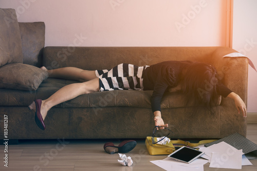 Obraz Business woman in dress feeling Exhausted and overworked working in the night on couch,Stress from overtime working concept. - fototapety do salonu