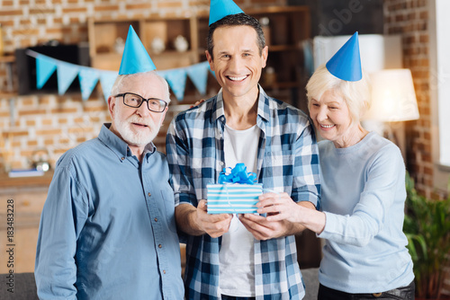 Upbeat Young Man Standing Between His Elderly Parents And Holding Birthday Gift While All Of Them Posing For The Camera Wearing Party See More
