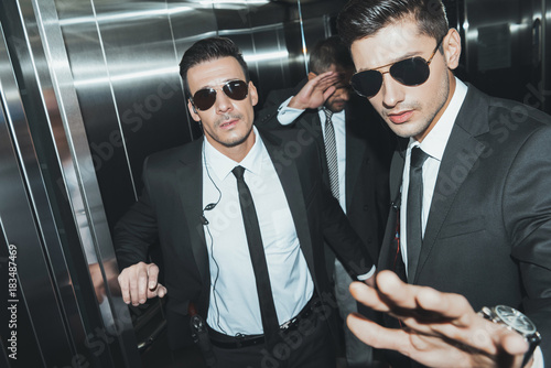 Cuadros en Lienzo  bodyguards stopping paparazzi and celebrity covering face with hand in elevator