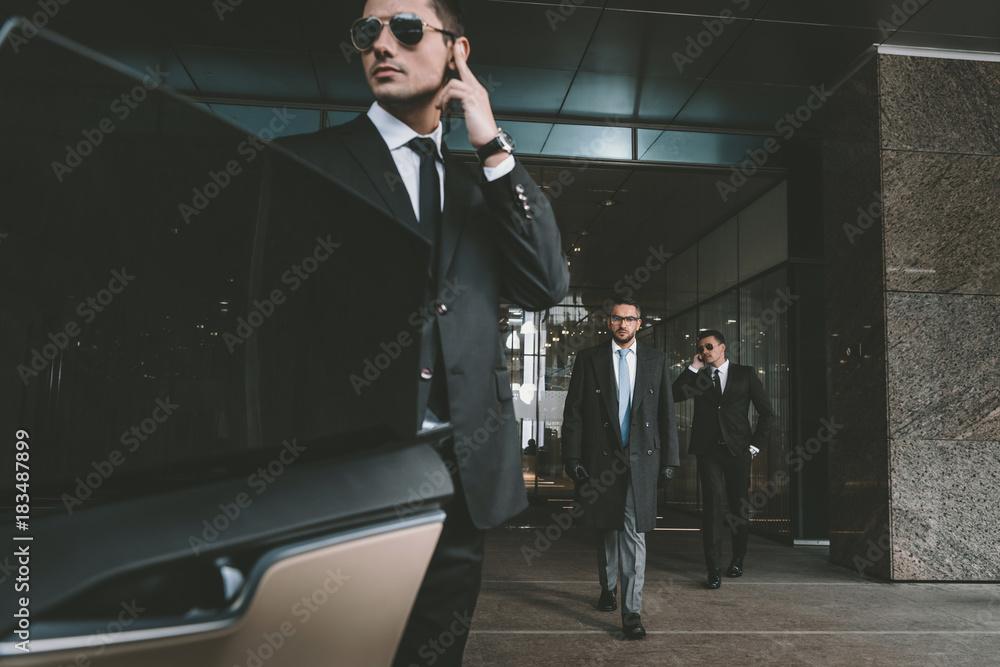 ochroniarz otwierający drzwi samochodu dla biznesmena