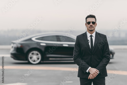 serious bodyguard standing with sunglasses and security earpiece on helipad Wallpaper Mural